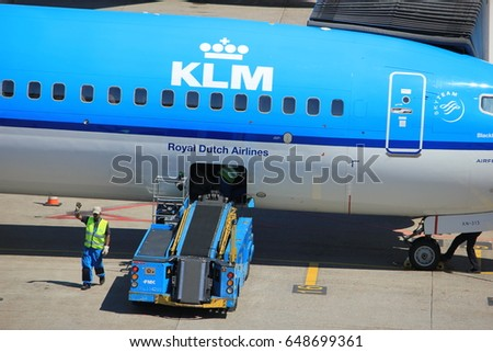 Amsterdam The Netherlands -  May 26th 2017: KLM Boeing 737 parked at gate at Schiphol International Airport, luggage handling