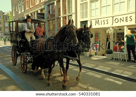AMSTERDAM, THE NETHERLANDS - MAY 8, 2016: The horses carriage in old street of Amsterdam, The Netherlands. A popular tourist attraction. Toned image