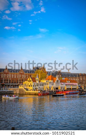 AMSTERDAM, THE NETHERLANDS - MAY 5, 2016: Traditional old buildings and boats at sunset in Amsterdam