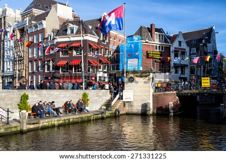 AMSTERDAM, THE NETHERLANDS - NOVEMBER 08: A view of the houses at the canal in Amsterdam, Holland on Nov 08, 2014. Relaxing by the canal is very popular way of spending time in Amsterdam. - stock photo