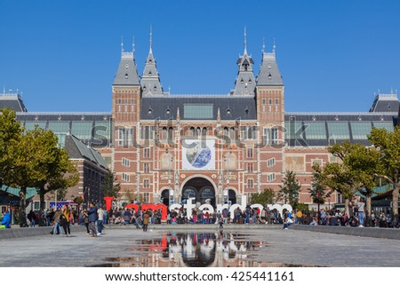 AMSTERDAM, THE NETHERLANDS - OCTOBER 11, 2015: A lot of tourists take photo in front of the Rijksmuseum, a popular destination in Amsterdam, The Netherlands, on OCTOBER 11, 2015 - stock photo