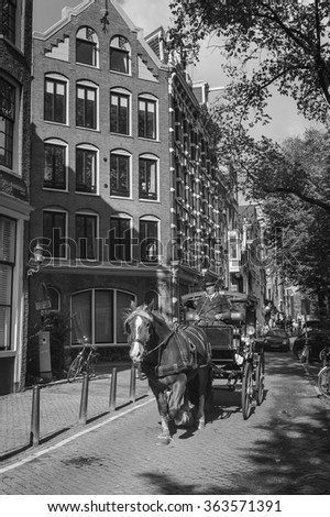 Amsterdam, The Netherlands - October, 2012. Carriage driven by old coachman in a street of the historical centre of Amsterdam.  - stock photo