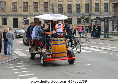 Amsterdam, the Netherlands -October 03, 2015: People riding beer bicycle in historical city centre
