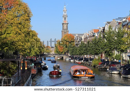 Amsterdam, The Netherlands - October 16, 2016: People sail in boats on a canal near the tower of the Westerkerk church with autumn trees in Amsterdam, The Netherlands on October 16, 2016