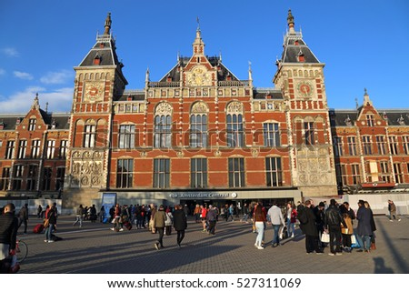 Amsterdam, The Netherlands - October 16, 2016: People walk in front of the central railway station in Amsterdam, The Netherlands on October 16, 2016