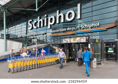 AMSTERDAM, THE NETHERLANDS - SEP 11: Airport entrance with passing travellers and a stewardess on September 11, 2014 at the airport Schiphol of Amsterdam, the Netherlands - stock photo