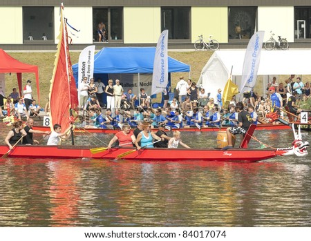 AMSTERDAM, THE NETHERLANDS - SEP 3: International Dragon boats teams and spectators participate in the water ritual at Dragon boats Regatta-2011, September 3, 2011, in Amsterdam, The Netherlands