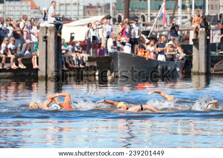 AMSTERDAM, THE NETHERLANDS - SEPT 9, 2012: Unidentified swimmers participate in The Amsterdam City Swim, 2028 meters crossing the city canals annual charity event - stock photo