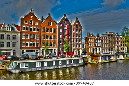 Amsterdam typical houses and houseboats in the canal, Netherlands. HDR photo. - stock photo