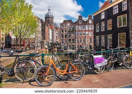 Amsterdam with  bicyclec on the bridge against canal, Holland - stock photo