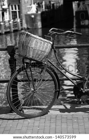Amsterdam with old bicycle on the bridge against canal, Holland - stock photo