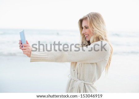 Amused blonde woman in wool cardigan taking a picture of herself with a tablet pc on the beach - stock photo