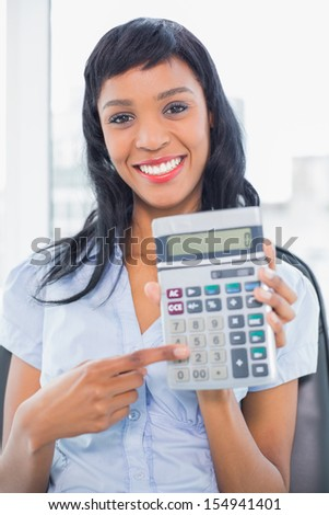 Amused businesswoman holding a calculator in office - stock photo