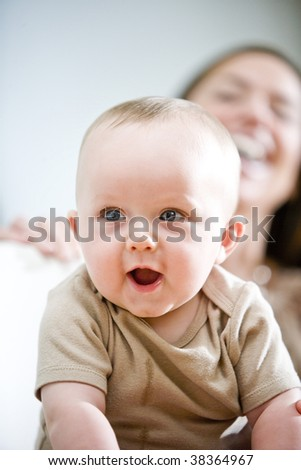 Amused six month old baby with mother laughing in background - stock photo