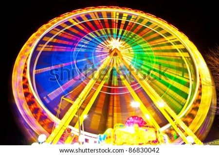 Amusement park at night background - ferris wheel in motion - stock photo