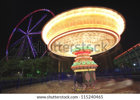 Amusement park at night - ferris wheel and carousel in motion
