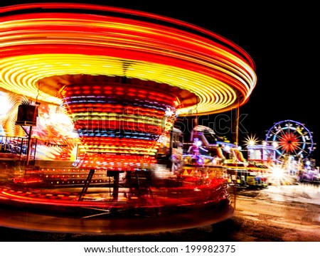 Amusement park at night - ferris wheel and roundabout in motion - stock photo