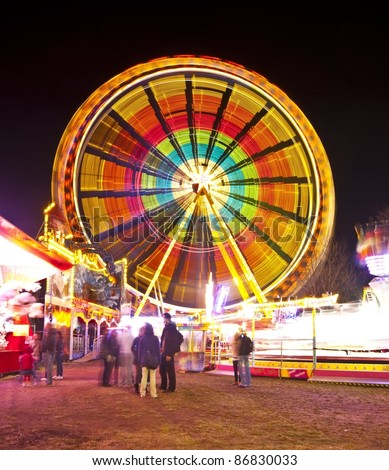 Amusement park at night - ferris wheel in motion - stock photo