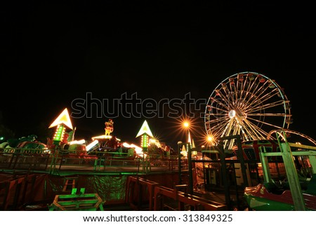 Amusement park at night with ferris wheel - stock photo