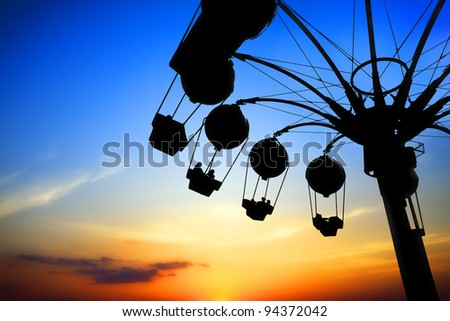 Amusement park at sunset - stock photo