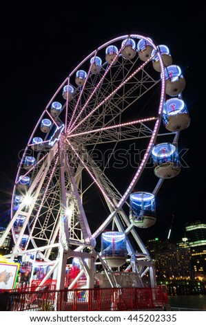Amusement park attractions. Spinning ferris wheel at night - stock photo