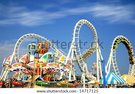 Amusement park rides with a very blue sky as background - stock photo