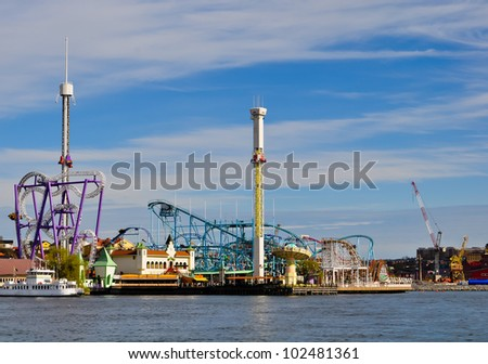 amusement park with colorful attractions at the waterfront in stockholm, sweden - stock photo