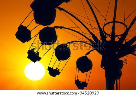 Amusement ride on golden sunset - stock photo