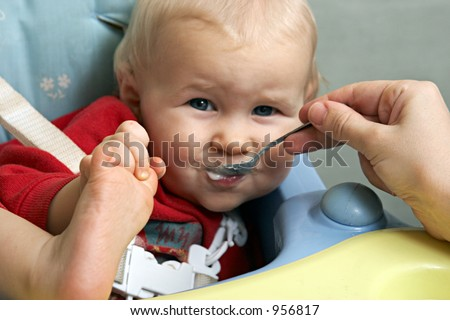 amusing baby with a spoon in a mouth - stock photo