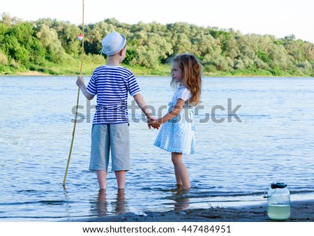 amusing boy and girl on the river summer day - stock photo