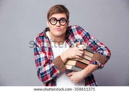 Amusing comical young male in round glasses and checkered shirt holding books over grey background