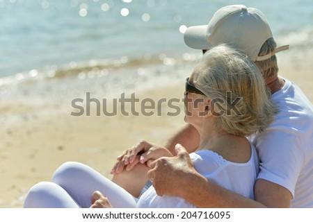 Amusing elderly couple having rest on beach - stock photo