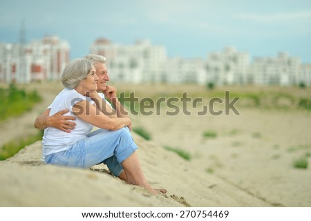 Amusing elderly couple having rest sitting on sand - stock photo