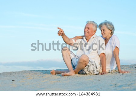 Amusing elderly couple went to the beach to enjoy the sea breeze - stock photo