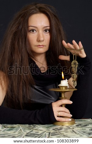 Amusing girl as a witch on a dark background - stock photo