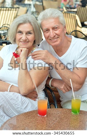 Amusing happy smiling old couple drinking juice at cafe