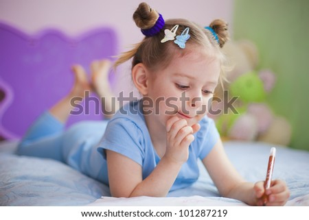 Amusing little girl painting in her nursery at home - stock photo