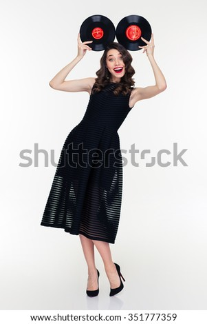 Amusing lovely cute girl with bright makeup in retro style having fun with vinyl records isolated over white background - stock photo