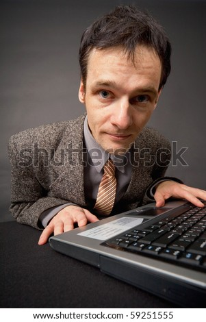 Amusing portrait of the young man on a workplace at dark office - stock photo