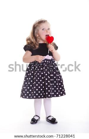 Amusing toddler girl in elegant dress with heart lollypop - stock photo