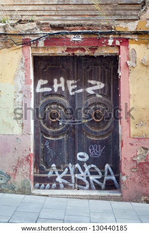 An abandoned building, formerly a restaurant. It's double door entrance is closed down with a chain and a lock, and covered in graffiti. Shot at the Sarri�  quarter of Barcelona (Spain). - stock photo