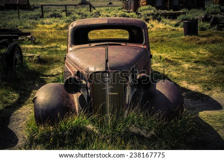 An abandoned car on the front lawn of a  prairie farm.
