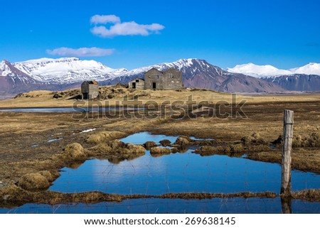 An abandoned farm-house sits on a wide open grass field with the background formed by the snow-capped mountains. The rivers and lakes are formed by the melting ice from the mountains. - stock photo