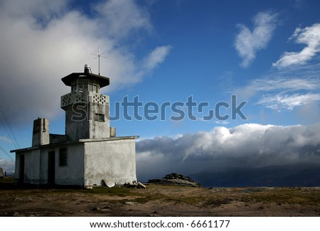 An abandoned fire lookout tower over a beautiful cloudy sky.