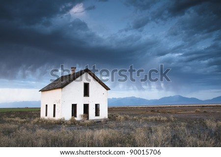 An abandoned house is overcome by a dark and eerie sky