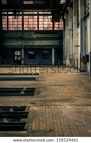 An abandoned industrial interior in dark colors - stock photo