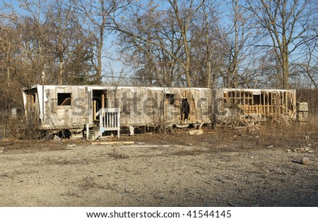 An Abandoned Mobile Home Set Among a Group of Trees