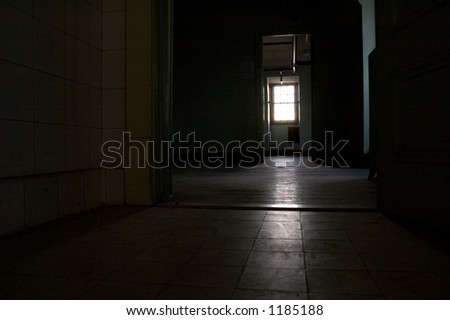 An abandoned room only lit by a window at the far end of the room.