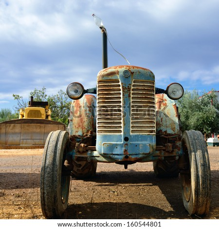 An abandoned rusty vintage tractor in countryside - stock photo