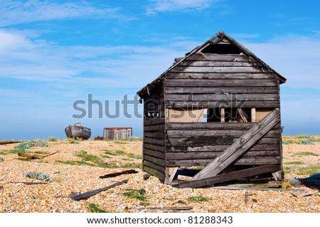 an abandoned shack on a shingle beach - stock photo